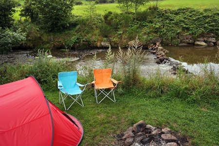 bourn: Campsite with a canvas tent and camp furniture near a creek