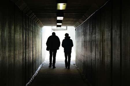 caminando: Dos personas caminan a la luz al final del túnel Foto de archivo