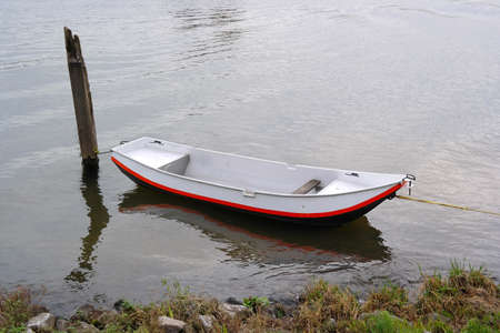 meuse: Old-fashioned iron moored row boat on the Meuse river in The Netherlands