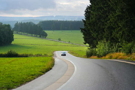 cantons: Car on winding road in a rainy Ardennes Landscape near Waimes in the Belgian East Cantons Stock Photo