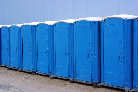 Una línea de baños portátiles. Fila de orinales porta en un acto público.