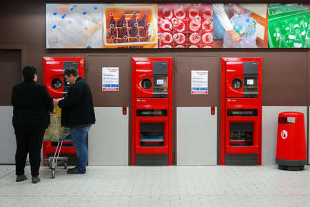 MEPPEN, GERMANY - MARCH 2016: Shoppers Their return bottles and cans or reusable packagings in a reverse vending machine or a Kaufland Hypermarket. Publikacyjne