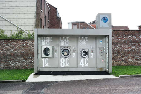 HERVE, BELGIUM - JULY 2015: Laveries Révolution, commercial washing machines and dryer in a self-service laundry. Explored by Kish Photomaton