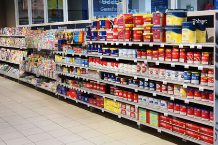 carrefour: MALMEDY, BELGIUM - JULY 2015: Aisle with Tobacco packings for a home Cigarette tubing machine in a Carrefour Hypermarket.