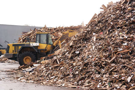 briquettes: Shovel accumulate a pile of wood chips for use as a biomass solid fuel. Stock Photo