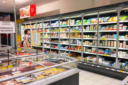Waldfeucht, GERMANY - MAY 2016: Woman shopping in the refrigerated fresh products aisle of an REWE supermarket. REWE supermarkets are part of the REWE Group, a diversified German retail and tourism group. Publikacyjne
