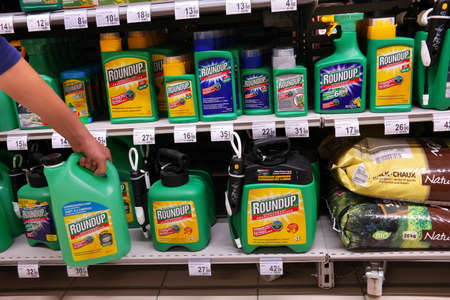 MALMEDY, BELGIUM - MAY 2016: Shelves with a variety of Herbicides in a Carrefour Hypermarket. Roundup is a brand name of an herbicide containing glyphosate, made by Monsanto Publikacyjne