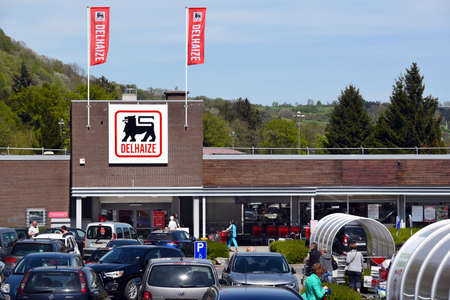 retailer: AYWAILLE, BELGIUM - MAY 6, 2016: Parking and entry of a Delhaize supermarket, part of Ahold, Delhaize Group, an Dutch-Belgian international food retailer.