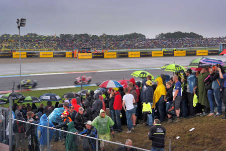 motorcycling: ASSEN, NETHERLANDS - JUNE 2016: Rain-soaked crowd on the Dutch TT, a motorcycling event.