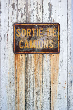 corrode: Sortie de Camions - Rusty sign in French with: truck exit, on a white painted wooden panel