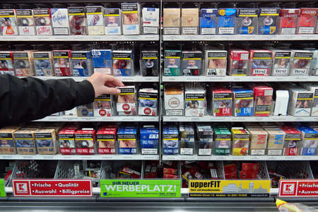 NORDHORN, GERMANY - DECEMBER 2016: packagings cigarettes near the checkout of a Kaufland Hypermarket. Pictures on cigarette packs warning of smoking dangers, thickening increased Attempts quit among smokers.