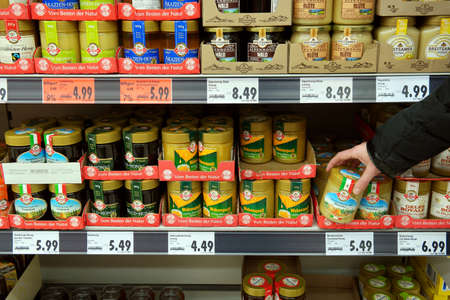 GERMANY - DECEMBER 2016: Shelves with various jars of honey in a Kaufland supermarket. Publikacyjne
