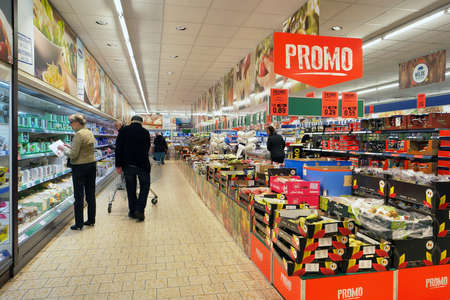 TURNHOUT, BELGIUM - OCTOBER 2016: Interior of a Lidl supermarket. Shopper choose in the refrigerated fresh products aisle. Lidl is a German discount chain with stores in 28 countries in Europe.