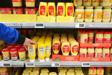 FLANDERS, BELGIUM - OCTOBER 2016: Aisle with various Mustard products in a Carrefour Hypermarket