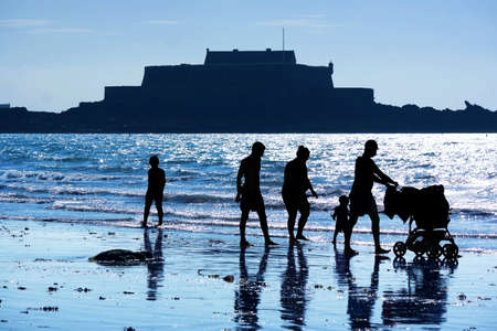 Silhouettes of a family at St. Malo beach walking along the sea at dusk. In the background the contours of Fort National.