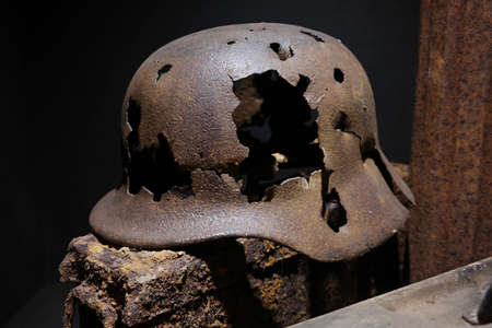 specifies: A rusty German World War II military helmet Pierced with bullets, remnant of the Battle of the Bulge, found in the ardennes.
