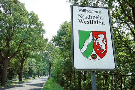 Welcome sign with the official coat of arms of the German state of North Rhine-Westphalia.