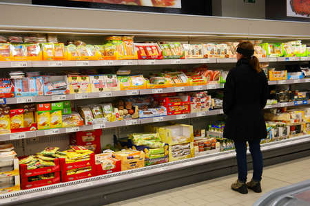 GERMANY - DECEMBER 2016: Shopper in the cooled fresh department of ALDI Nord discount supermarket.