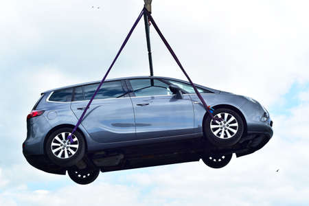 Flying car. Vehicle lifted up for loading on board of a ship