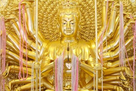 Statue of Guan Yin Thousand Hand glittering gold.  photo