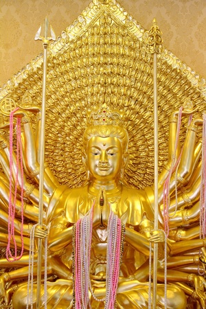 Statue of Guan Yin Thousand Hand glittering gold.  photo