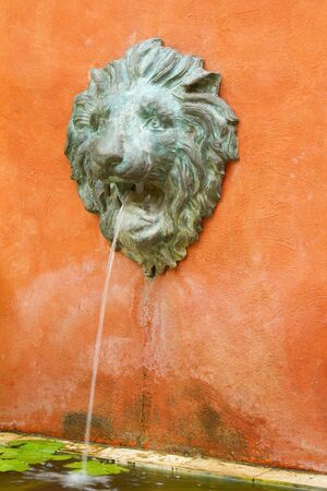 merman: water flow from statue head of lion in the garden  Stock Photo