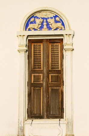 Thai old wooden door with white wall photo