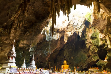 Buddha images and natural light at the end of the cave  photo