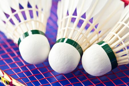 Badminton rackets and shuttlecock isolated on blue background photo