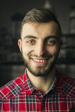 sincerely: A studio shot of young man looks into camera with sincerely smiling face expression