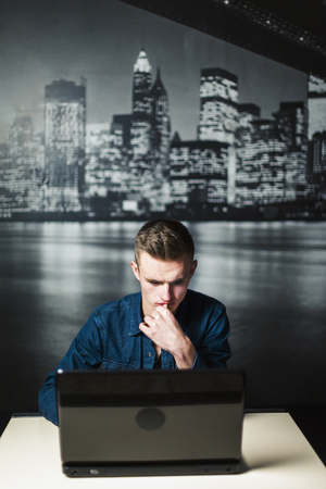 A studio shot of an young attractive man using black laptop on white table before night city wallpaper Stock Photo