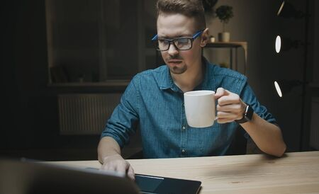 Man holding cup looking at laptop