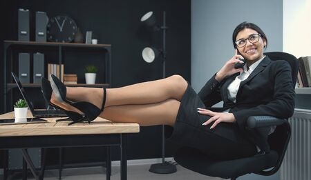 Carefree business girl in formal clothing talking on mobile phone sitting in a chair with her legs on office desk