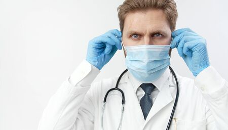 Potrait of practitioner putting on protective mask, having stethoscope, and blue surgical gloves while looking at camera isolated light background