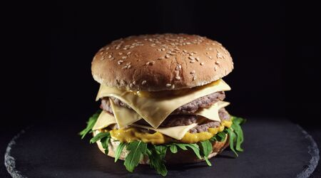 Closeup of king size cheeseburger isolated on black background Stock Photo