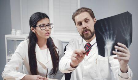 Two doctors discussing patients hands xray image, preceptor showing roentgenogram details to intern