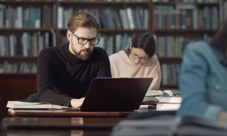 Absorbed adult man in glasses working on laptop sitting in public library reading hall around people