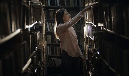 Concentrated girl looking for book in bookcase in dark library standing between rows of shelves