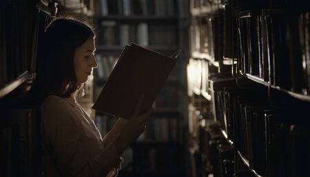 Young woman rapt in reading in dark library standing among rows of shelves with books Stock Photo