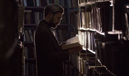 Man consumed with reading in dark library standing among rows of shelves with books, side view Stock Photo