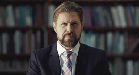 Portrait of serious bearded middle-aged businessman looking camera over library bookcase background