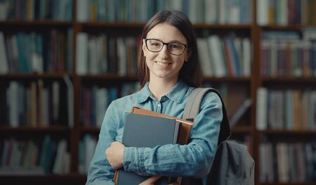 Portrait of lovely smiling female student with glasses and backpack holding books looking camera
