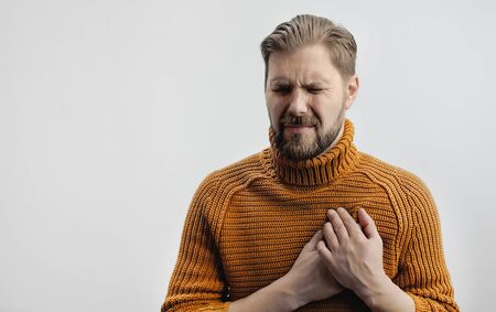 Portrait of grimacing bearded man placing hands on chest suffering from heartache, isolated
