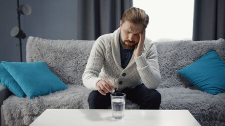 Middle-aged man sitting on sofa suffering headache touching temple putting aspirin to glass of water