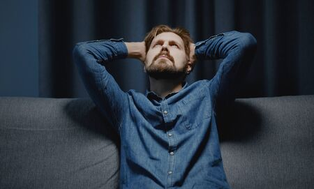 Mature bearded man in jeans shirt holding head with hands looking up sitting on sofa, dark interior