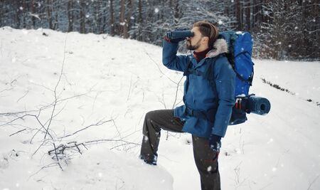 Side view of male backpacker looking into distance through binocular with one leg on log, woods edge Standard-Bild