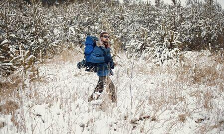 Backpacker walking at snowy forest edge enjoying winter nature wilderness