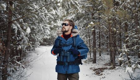Front view of mature bearded man walking through forest enjoying winter nature, half-body image