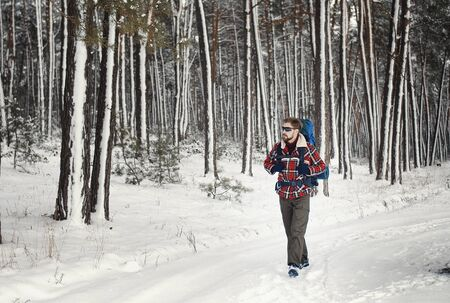 Backpacker equipped with trekking gear walking along snowy pine forest trial in winter