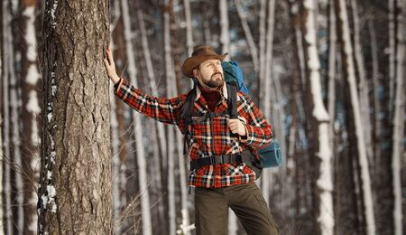 Adult bristled backpacker and with hiking gear enjoying winter scenery, selective focus